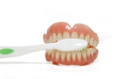 Falsche Zähne und Zahnbürste Stockfotos