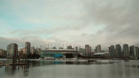 False Creek Cityscape Timelapse, Vancouver. A time lapse view of downtown Vancouver and the calm water of False Creek where dragon boat teams practice. British stock video footage