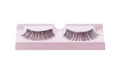 False eyelashes pair on pink display isolated on white. Background royalty free stock images