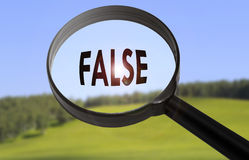 False. Magnifying glass with the word false on blurred nature background. Searching false concept stock image