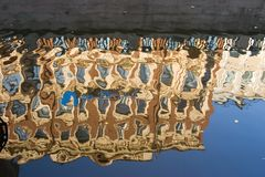 False mirror. Reflection in the river of the house on quay Stock Image