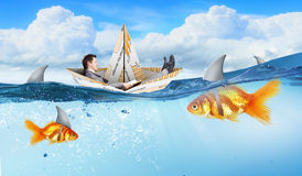 False risk for your business. Concept of fake threat when businessman float in paper ship and sharks in water appear to be goldfish Royalty Free Stock Photography