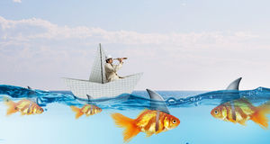 False risk for your business. Concept of fake threat when businessman float in paper ship and sharks in water appear to be goldfish Stock Photography