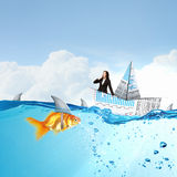 False risk for your business. Concept of fake threat when businesswoman float in paper ship and sharks in water appear to be goldfish Royalty Free Stock Photography