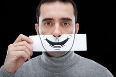 False smile. A man showing a blank, indifferent expression, holding a paper with a smile drawn on it in front of his face Stock Photo