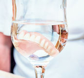 False teeth in glass of water Stock Photography