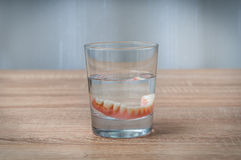 False teeth swim in transparent water glass Stock Photography