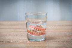 False teeth swim in transparent water glass Royalty Free Stock Photography
