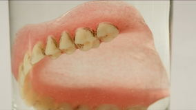 False teeth in water glass stock video footage