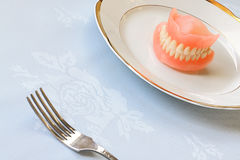 False teeth on white plate Stock Photos