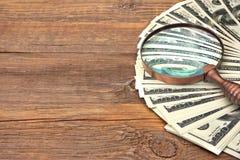 Falsificazione cento banconote del dollaro sotto la lente d'ingrandimento Immagine Stock