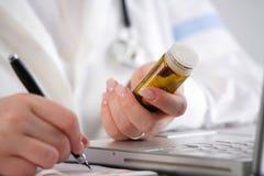 Falsifichi la scrittura della prescrizione con le pillole in sua mano Immagine Stock Libera da Diritti