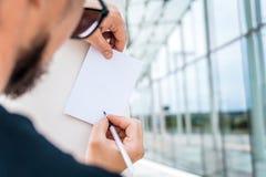 Falsk övre anteckningsbok i en mans hand, mot bakgrunden av pelarna och exponeringsglasbyggnaden arkivbild
