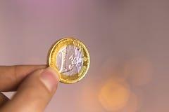 Falskt euro av choklad mellan fingrarna av en kvinna royaltyfri foto