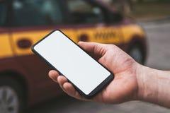 Falskt upp av en smartphone i hand, på bakgrunden av en taxibil arkivbild
