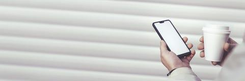 Falso para arriba de un smartphone y de una taza plástica con café en las manos de un individuo en un fondo blanco imagenes de archivo