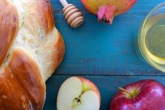 Falt lägger sikt av den runda söta challahen, honungkruset, det röda äpplet och p Arkivfoton
