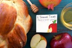 Falt lägger sikten av det Shana Tova kortet som omges av rund söt chall Arkivfoton