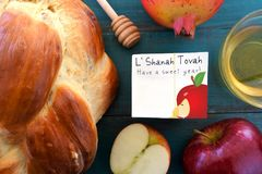 Falt lay view of Shana Tova card surrounded by round sweet chall. Ah, honey jar, red apple and pomegranate on a turquoise background. Rosh Hashanah Jewish new Stock Photos