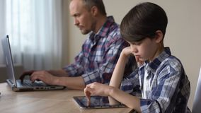 Falta da atenção dos pais, criança que joga o jogo na tabuleta quando paizinho que usa o portátil vídeos de arquivo