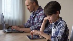 Falta de atención de los padres, niño que juega al juego en la tableta mientras que papá que usa el ordenador portátil almacen de metraje de vídeo