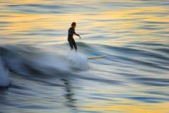 Falta de definición 2 de la persona que practica surf de la puesta del sol Fotografía de archivo