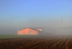 Falta de definición abstracta feding el granero rojo en granja con el cielo azul en invierno Foto de archivo libre de regalías