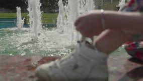 Falta de definición de la muchacha que se sienta cerca de la fuente y que ata los zapatos del deporte Opinión de cámara lenta almacen de metraje de vídeo