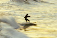 Falta de definición de la persona que practica surf de la puesta del sol Imágenes de archivo libres de regalías