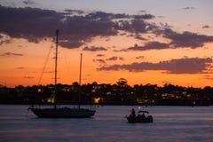 Falta de definición de las siluetas del barco en el mar en la costa por puesta del sol Fotografía de archivo libre de regalías