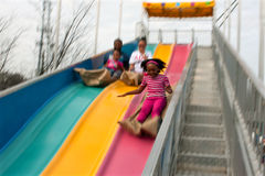 Falta de definición de movimiento de la familia que desliza abajo la diapositiva de la diversión en la feria Imagen de archivo