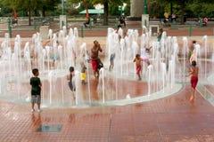 Falta de definición de movimiento de las familias que juegan en fuente en el parque de Atlanta Imagenes de archivo