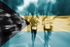 Falta de definición de movimiento del corredor de maratón con la mezcla de la bandera de Bahamas Fotos de archivo libres de regalías