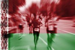 Falta de definición de movimiento del corredor de maratón con la mezcla de la bandera de Bielorrusia Imágenes de archivo libres de regalías