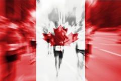Falta de definición de movimiento del corredor de maratón con la mezcla de la bandera de Canadá Foto de archivo
