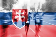 Falta de definición de movimiento del corredor de maratón con la mezcla de la bandera de Eslovaquia Fotografía de archivo libre de regalías