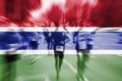Falta de definición de movimiento del corredor de maratón con la mezcla de la bandera de Gambia Imagen de archivo libre de regalías