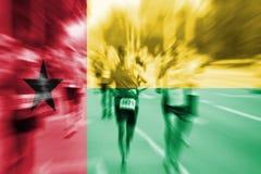 Falta de definición de movimiento del corredor de maratón con la mezcla de la bandera de Guinea-Bissau Fotos de archivo libres de regalías