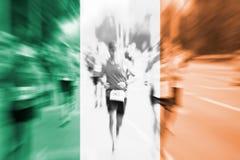 Falta de definición de movimiento del corredor de maratón con la mezcla de la bandera de Irlanda Imágenes de archivo libres de regalías