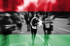 Falta de definición de movimiento del corredor de maratón con la mezcla de la bandera de Libia Imagen de archivo libre de regalías
