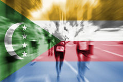 Falta de definición de movimiento del corredor de maratón con la mezcla de la bandera de los Comoro Imagen de archivo libre de regalías