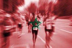Falta de definición de movimiento del corredor de maratón con la mezcla de la bandera de Marruecos Fotografía de archivo