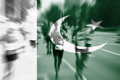 Falta de definición de movimiento del corredor de maratón con la mezcla de la bandera de Paquistán Fotos de archivo libres de regalías