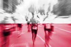 Falta de definición de movimiento del corredor de maratón con la mezcla de la bandera de Polonia Fotos de archivo libres de regalías