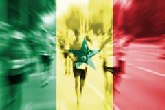 Falta de definición de movimiento del corredor de maratón con la mezcla de la bandera de Senegal Foto de archivo libre de regalías