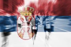 Falta de definición de movimiento del corredor de maratón con la mezcla de la bandera de Serbia Imagen de archivo libre de regalías
