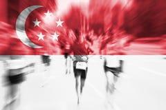 Falta de definición de movimiento del corredor de maratón con la mezcla de la bandera de Singapur Foto de archivo