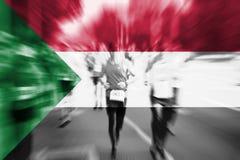 Falta de definición de movimiento del corredor de maratón con la mezcla de la bandera de Sudán Imágenes de archivo libres de regalías