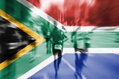 Falta de definición de movimiento del corredor de maratón con la mezcla de la bandera de Suráfrica Foto de archivo libre de regalías