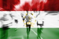 Falta de definición de movimiento del corredor de maratón con la mezcla de la bandera de Tayikistán Imagen de archivo libre de regalías